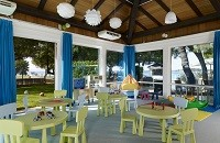 Medulin hotel's Kid's Club with green chairs and tables