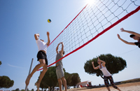 Four players on a sunny volleyball court near Medulin resort