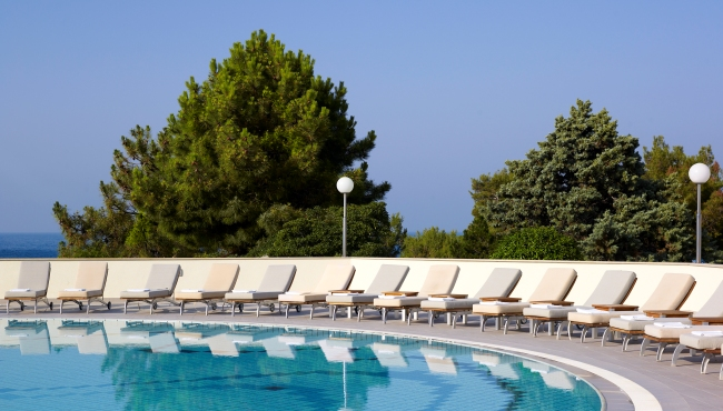 Lounge chairs surrounding circular hotel pool in Pula, Istria