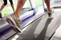 Person in tennis shoes running on a treadmill