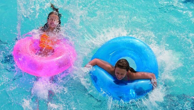 Kids in pink and blue inner tubes splashing in the pool