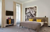 Hotel room with storage unit and grey bed with yellow pillows