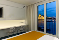 Hotel room with bed, work desk and view of Danube