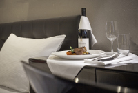 In-room dining with a steak and a bottle of champagne