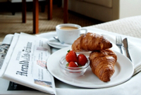Newspaper beside a plate of strawberries and croissants