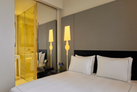 white bed with yellow lamp and glass bathroom