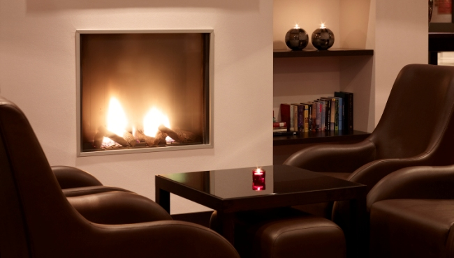 Hotel lounge with a fireplace and bookshelf in Eindhoven