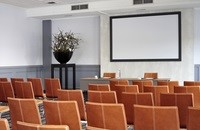 Leather chairs facing flower arrangement and projector screen
