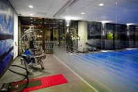 Hotel fitness centre with exercise equipment and a pool