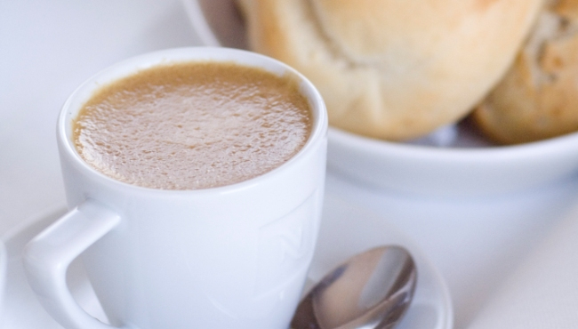 White cup with warm drink by basket of bread
