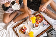 Two people sharing coffee and breakfast in bed