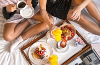 Two people sharing breakfast featuring coffee, orange juice, fruit and granola