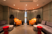 Smoking lounge with orange armchairs and red side tables