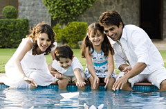 Smiling family sitting on edge of pool