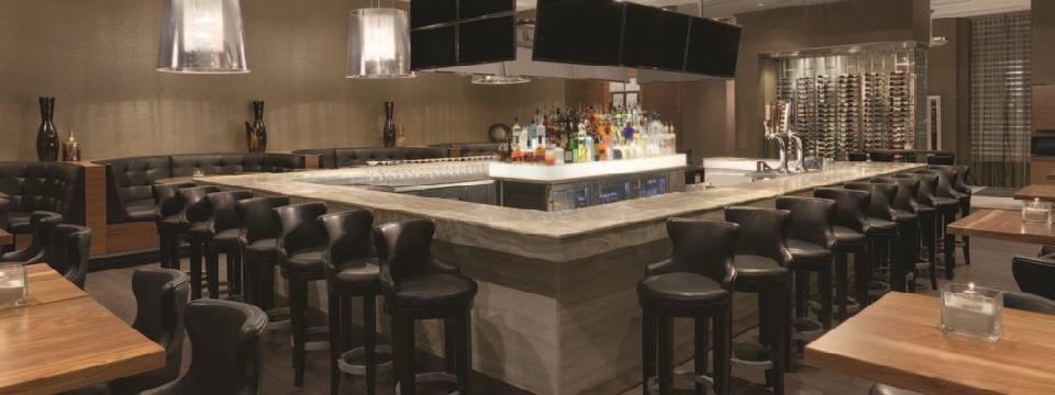Hotel lounge with bar seating, table seating and TVs