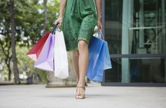 Woman in a green dress carrying several shopping bags