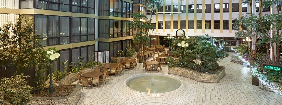 Atrium with tables, water fountain, lamppost lighting and plants
