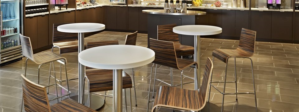 On-site cafe with wood-patterned chairs and white tables