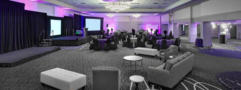 Ballroom with stage, lectern, platform, uplights and a mix of seating styles