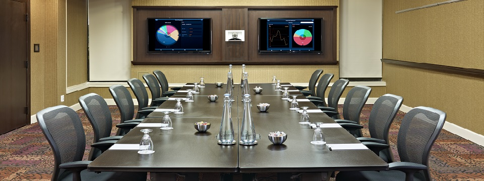 Meeting space with two wall-mounted screens for digital presentations