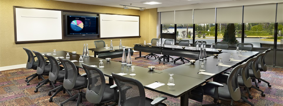 Meeting room in u-shape setup with whiteboards and mounted TV