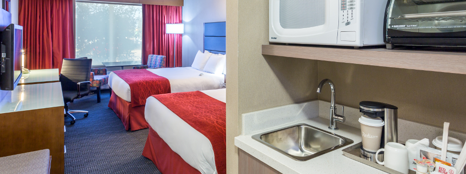 Hotel room with two beds, microwave and sink