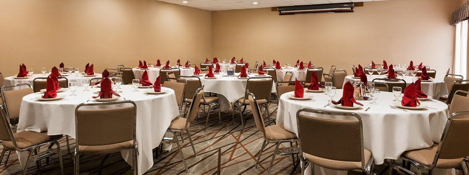 Meeting room set with round banquet tables and red accents