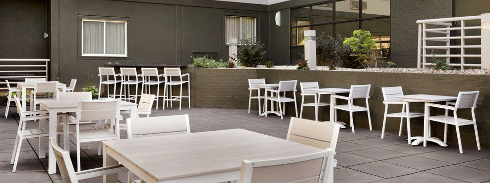 Outdoor patio area with clusters of white tables and chairs