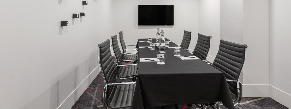 Boardroom with a conference table and a wall-mounted flat-screen TV