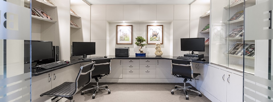 Business centre with white cabinetry, three computers and desk chairs
