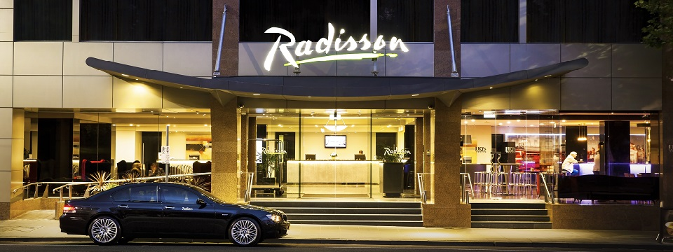 Car in front of Radisson on Flagstaff Gardens lit up at night