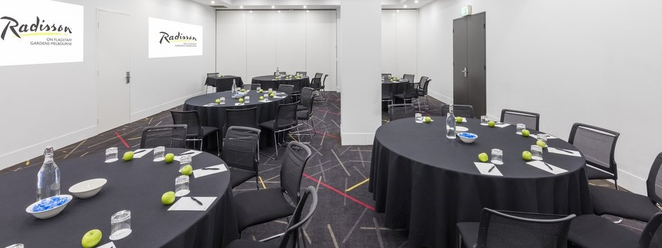 Meeting room arranged cabaret style with black chairs and tablecloths