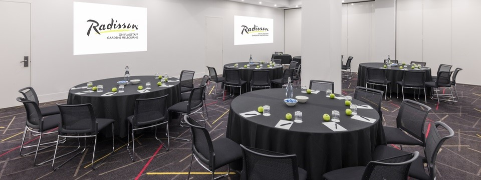 Cabaret-style meeting room setup with black chairs