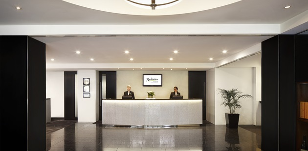 Sleek hotel lobby with white front desk and two staff members