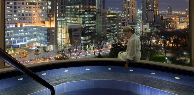 Rooftop spa looking out onto Melbourne with lady sitting on edge of spa