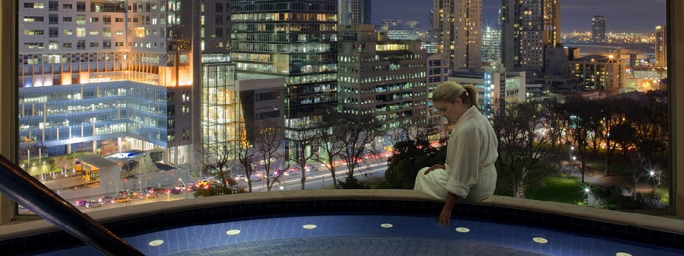 Rooftop spa overlooking Melbourne with a lady sitting on the edge of the spa
