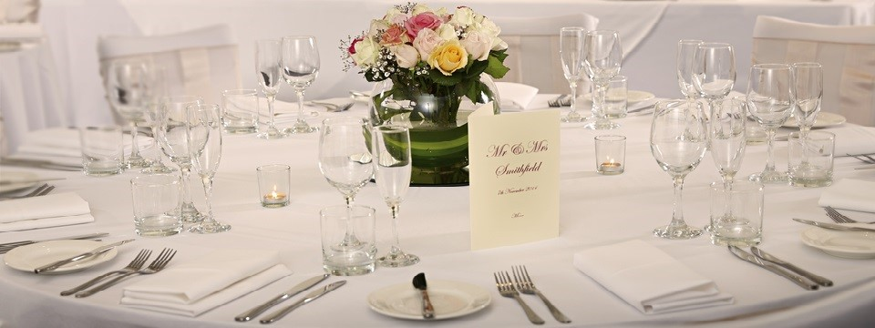 Round table set for a wedding reception with place settings