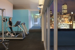 Gymnasium with views of Melbourne and woman on treadmill