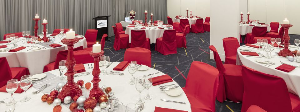 Banquet hall featuring round tables with red and white Christmas decorations