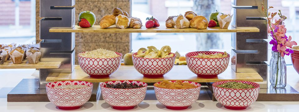 Breakfast spread featuring pastries and bowls of cereals and dried fruits