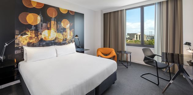 Guest room with a king bed, orange armchair and views over Flagstaff Gardens