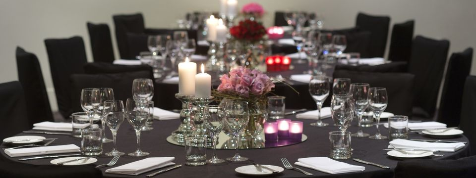Banquet tables set with dinnerware, candles, and pink and red flowers