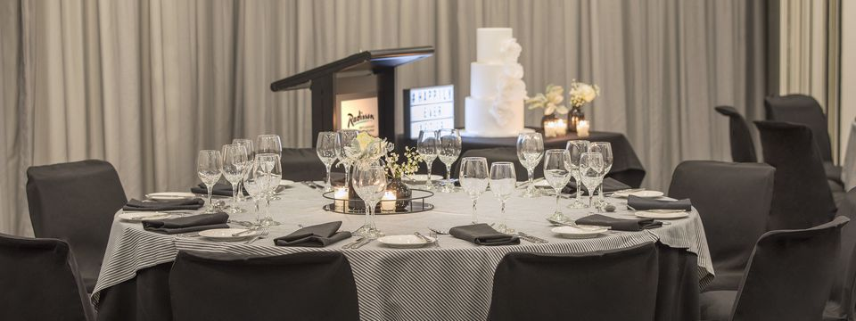 Three-tier wedding cake and black and white banquet tables at a reception