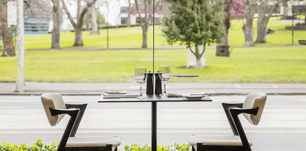 Table for two next to a glass wall with park views