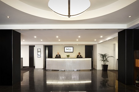 Sleek hotel lobby with front desk and two staff members