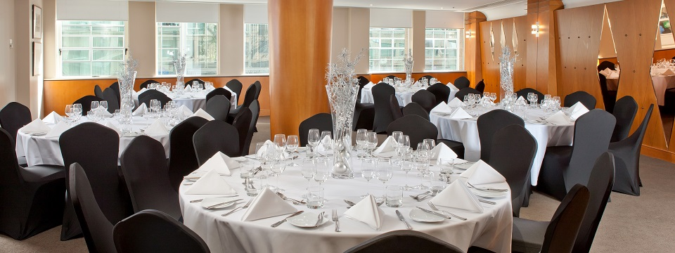Banquet space with round tables in black and white linens
