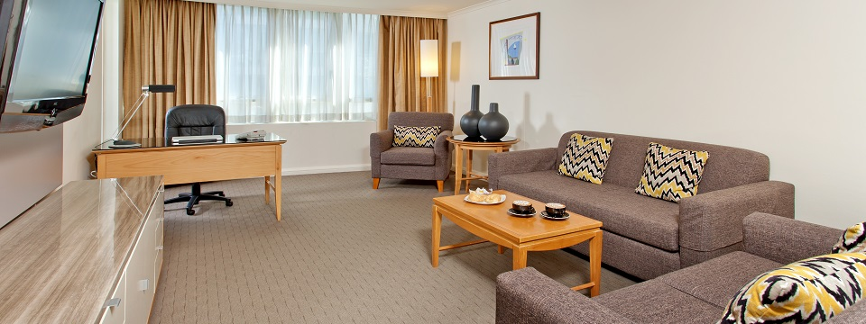 Hotel suite seating area with sofa, armchair and work desk