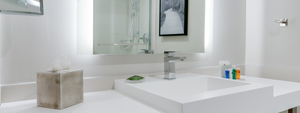 Suite bathroom with a sparkling white sink and colorful travel toiletries