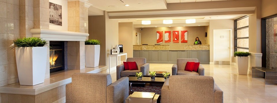 Understated fireplace and gray armchairs in hotel lobby