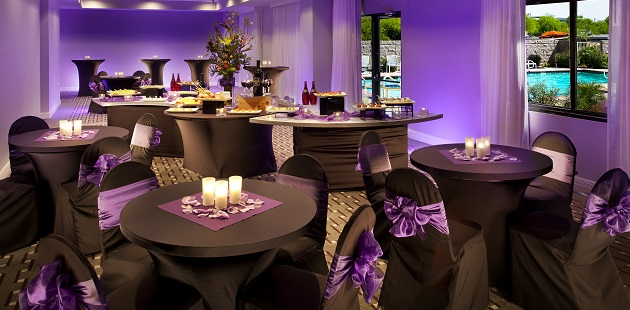 Black-and-purple decor in event venue with purple up-lighting